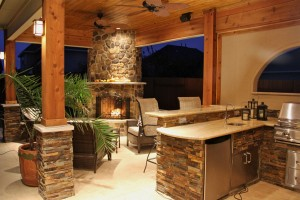Outdoor kitchen design includes stacked stone, fireplace