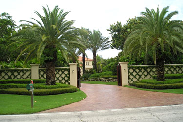 Sylvester Palms and structured landscaping create a tropical Mediterranean effect for this estate entry.