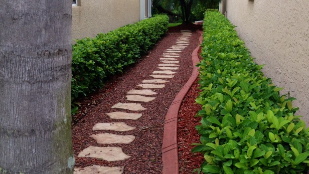 Stepping stones set in Alabama Crimson decorative stone and edged with concrete edging are a perfect solution for wet areas between homes.