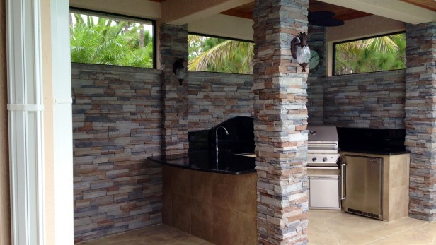Outdoor Kitchen features stacked stone finishes and new roof extending off of house.